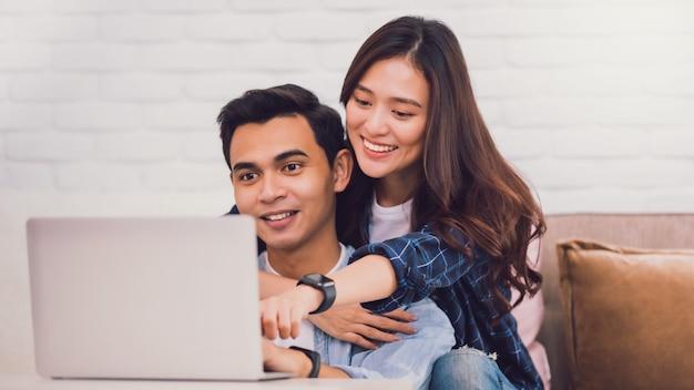 自宅の部屋で一緒にラップトップで働く若いアジアのカップルの恋人