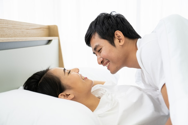Young asian couple making love together on the bed.