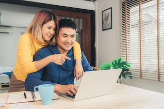 Young asian couple managing finances, reviewing their bank accounts using laptop computer