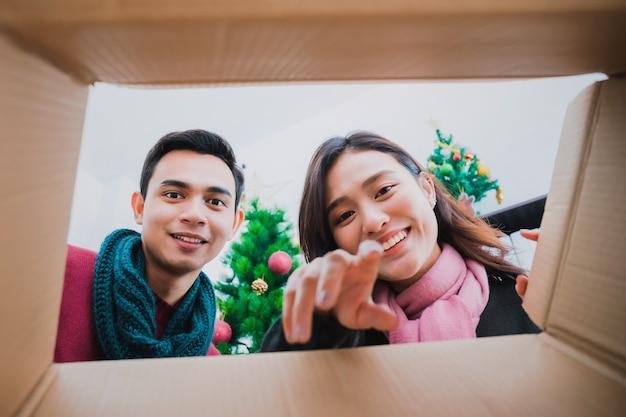 若いアジアのカップルがギフトボックスを開きます