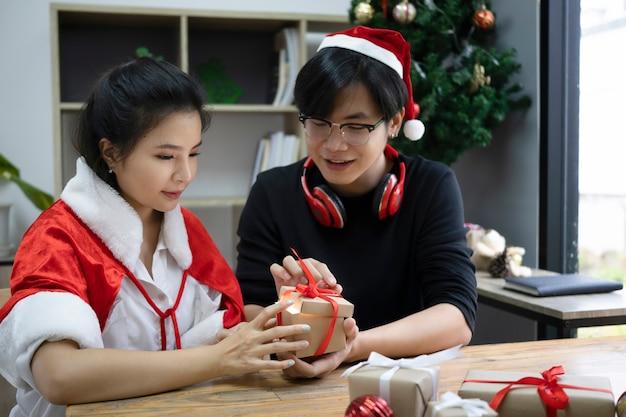 젊은 아시아 부부가 함께 거실에서 크리스마스 선물 상자를 엽니다.