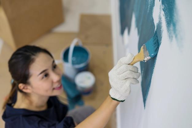 Молодая азиатская пара живопись внутренней стены с кистью