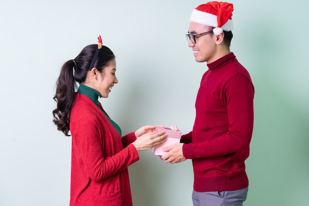 Young asian couple posing on green background with christmas concept