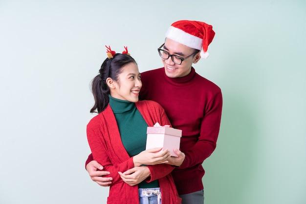 크리스마스 컨셉으로 녹색 배경에 포즈를 취하는 젊은 아시아 커플