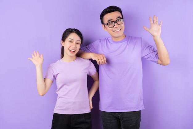 보라색 배경에 포즈를 취하는 젊은 아시아 커플