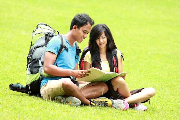 若いアジアのカップルが地図を読んで、草の上に座っています。