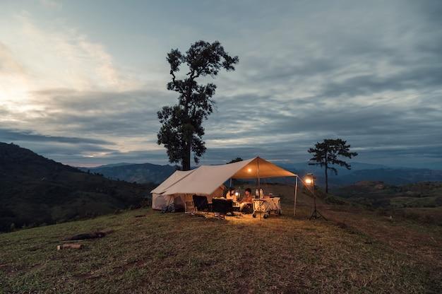 시골에서 저녁에 언덕에 던진 큰 텐트에서 쉬고 있는 젊은 아시아 커플