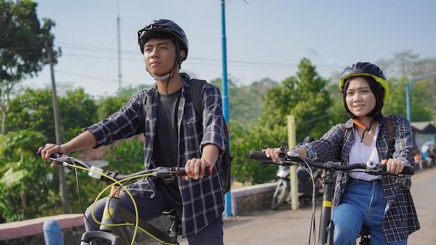 젊은 아시아 부부는 함께 자전거를 타고 일하러 간다