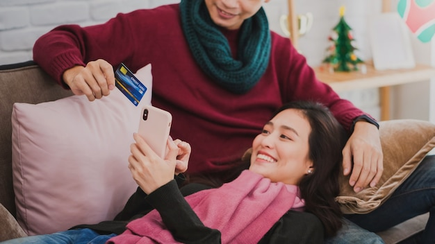 クレジットカードとスマートフォンでオンラインショッピングをする若いアジア人カップル