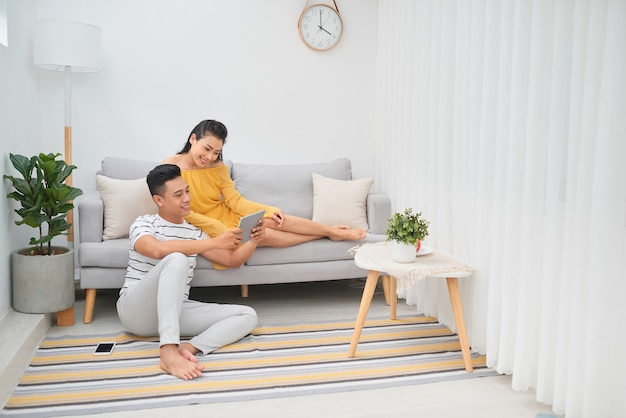 Young asian couple sitting on couch at home, using a tablet pc for internet and social media.