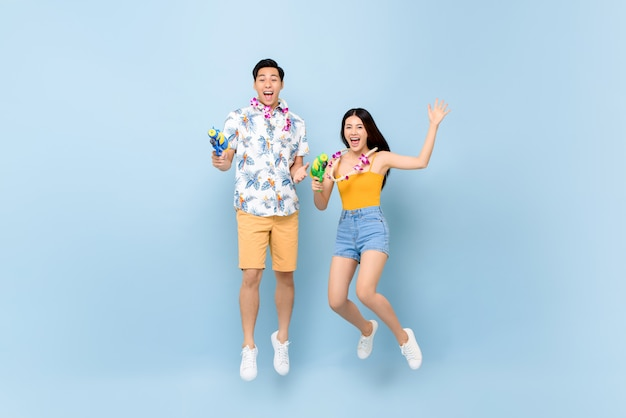 Young asian couple in summer outfits with water guns jumping for songkran festival in thailand and southeast asia