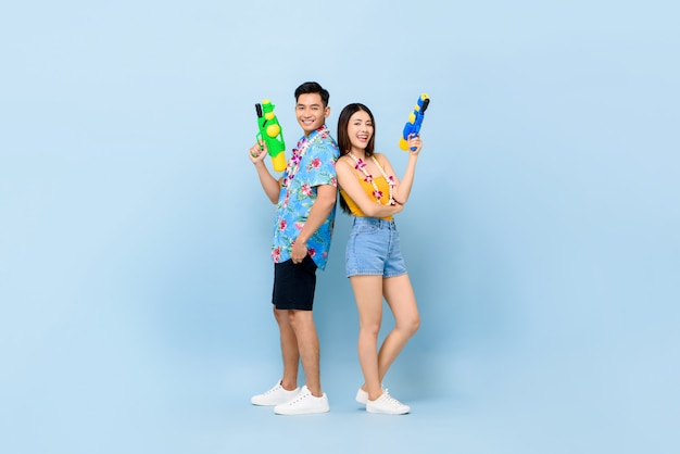 Young asian couple in summer outfits with water guns for songkran festival in thailand and southeast asia