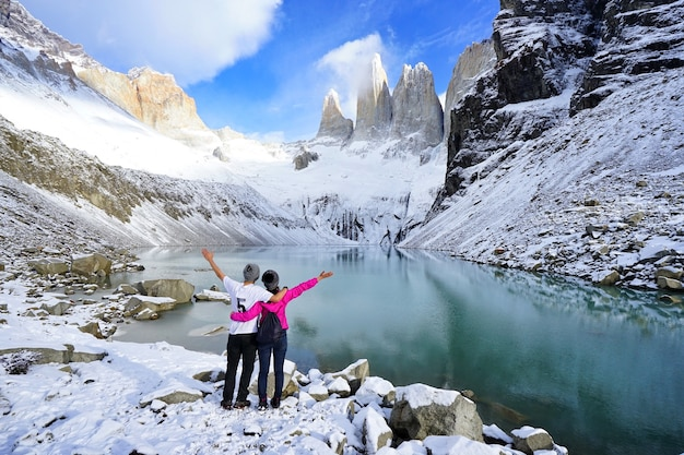 The young asian couple travellers standing with joy at torres del paine, patagonia in chil