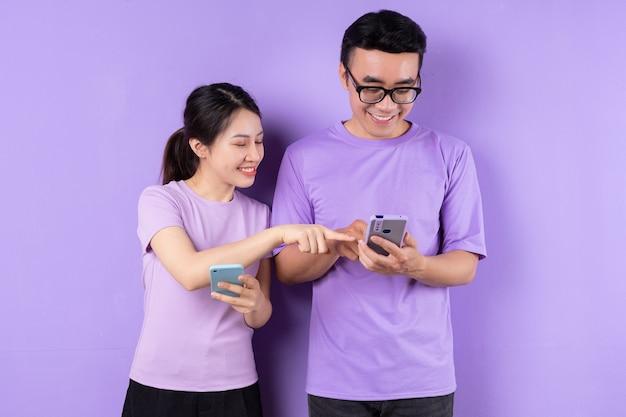 Молодая азиатская пара с помощью смартфона на фиолетовом фоне