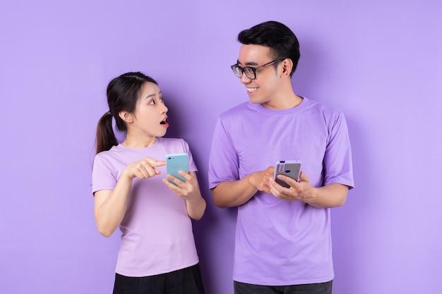 보라색 배경에 스마트폰을 사용하는 젊은 아시아 부부