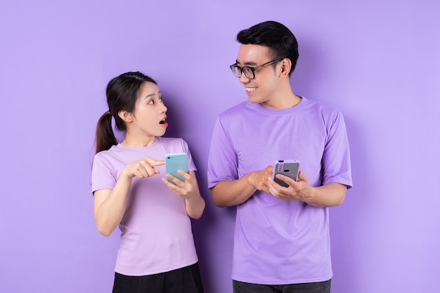 Young asian couple using smartphone on purple background