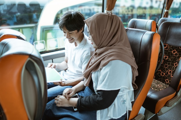A young asian couple using a tablet and looking at the screen together while sitting on the bus