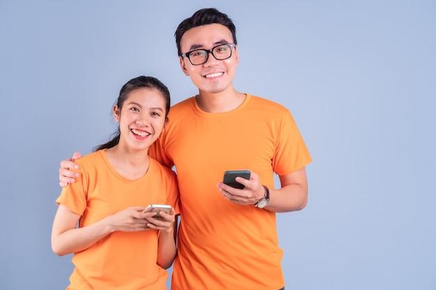 Молодая азиатская пара в оранжевой футболке на синем фоне