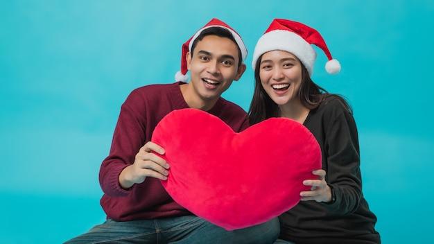 サンタクロースの帽子をかぶって赤いハートを持っている若いアジアのカップル