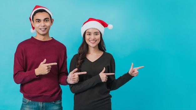 サンタクロースの帽子をかぶって指さしている若いアジアのカップル