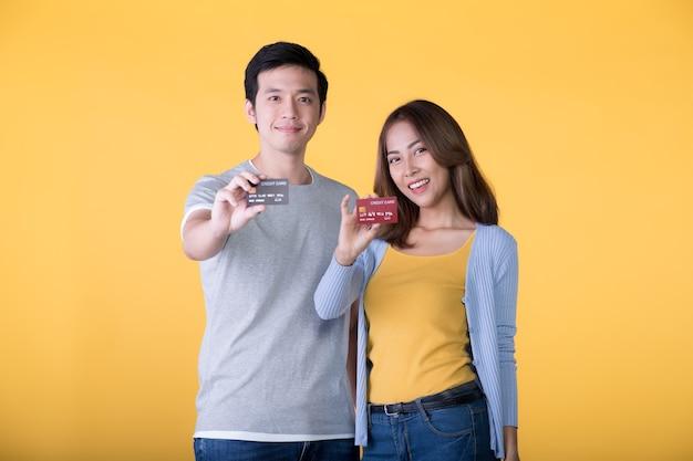 노란색 벽에 고립 된 신용 카드와 함께 젊은 아시아 부부
