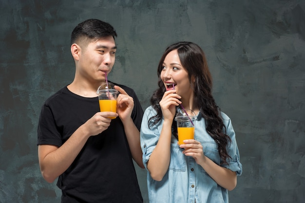 Young asian couple with  glasses of orange juice