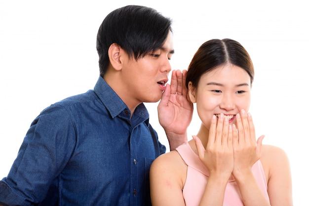 Молодая азиатская пара с мужчиной шепчет женщине, смеющейся