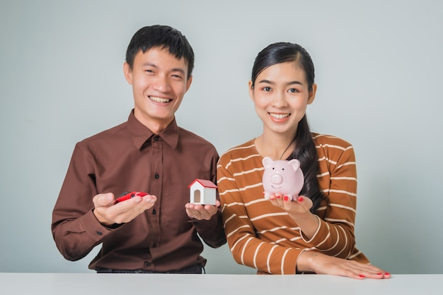 Young asian couple with piggy bank and toy house and car