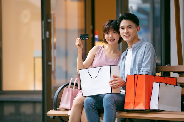 Young asian couple with shopping bags and credit card