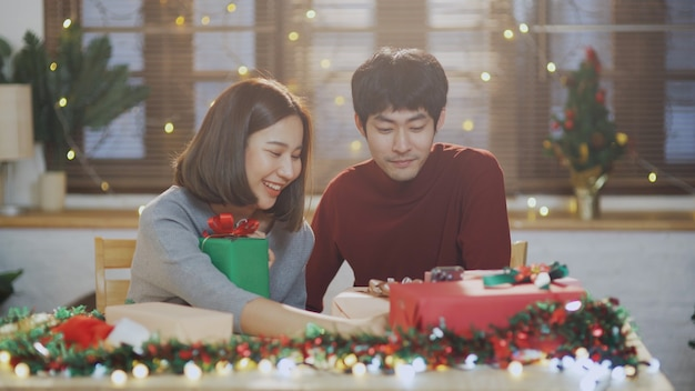 휴일 파티를 축하하기 위해 선물 상자를 포장하는 젊은 아시아 커플