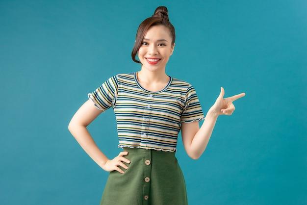 若いアジアのかわいい女性は、人差し指を離れて陽気に笑みを浮かべて分離しました。
