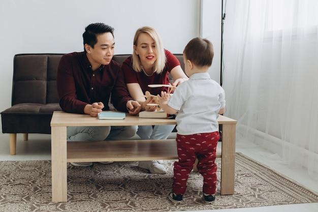 若いアジアのお父さんとヨーロッパの金髪のお母さんは明るい部屋で彼女の息子と一緒に座って遊ぶ