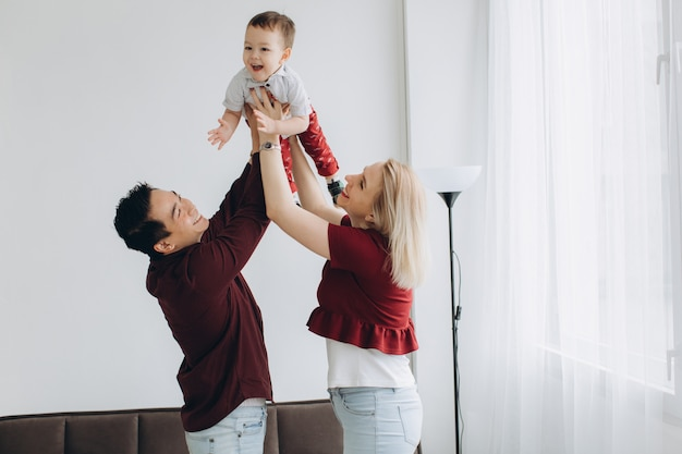 Young asian dad and european blonde mom hold son in her arms in bright room. multicultural trendy concept
