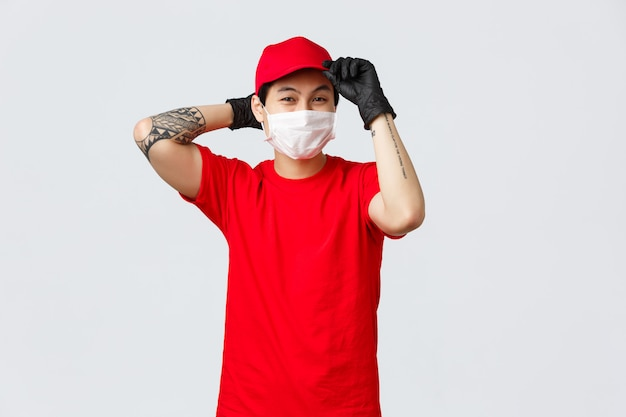 Young asian delivery guy put on red cap, wear medical mask and gloves, get ready deliver parcel to client, covid-19 pandemic safety measures for carriers. courier ensure fast shipping