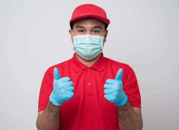 Молодой азиатский курьер в униформе в защитной маске и резиновых перчатках