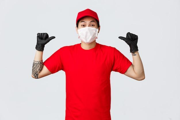 Молодой азиатский работник доставляющий покупки на дом указывает палец