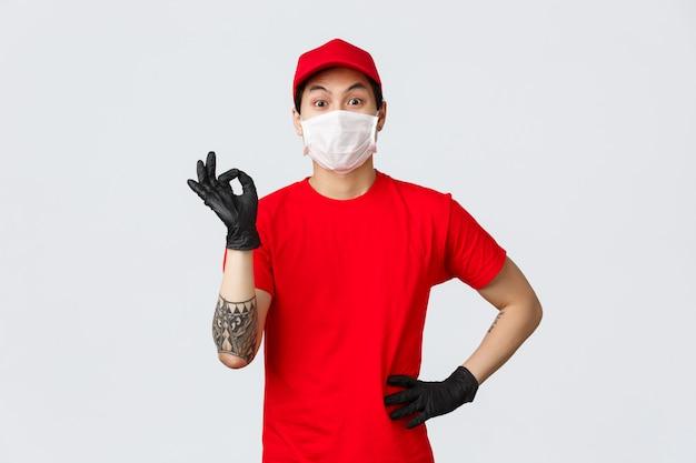 Молодой азиатский работник доставляющий покупки на дом показывает одобренный знак