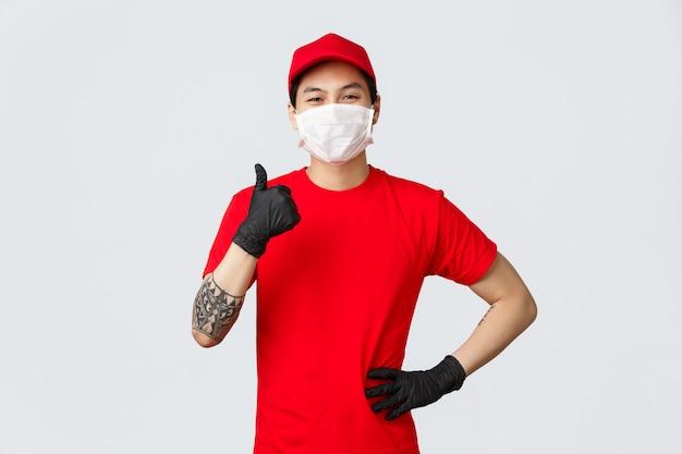 Молодой азиатский работник доставляющий покупки на дом показывает большой палец руки вверх