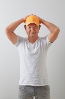 A young asian delivery man wearing an orange hat on light grey surface