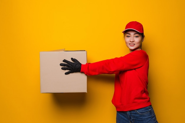 Young asian delivery woman holding box isolated on yellow