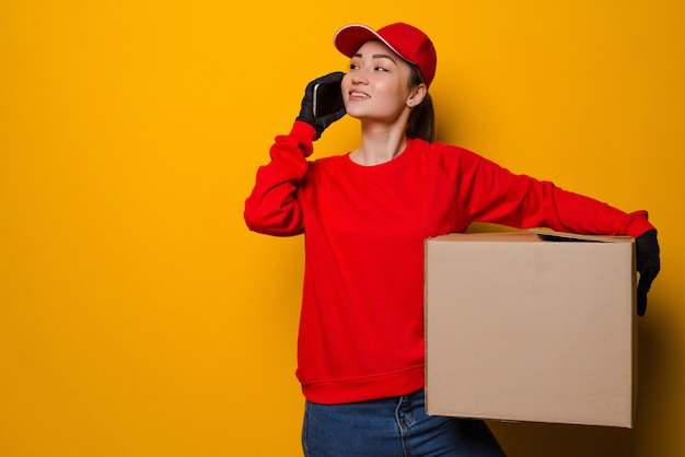 Young asian delivery woman holding box talking on the phone isolated on yellow wall