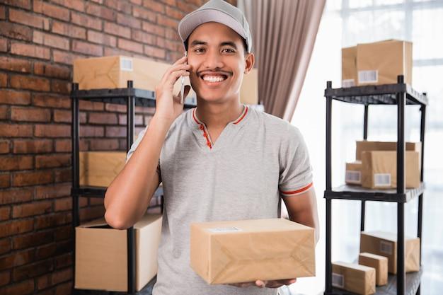 Молодой азиатский работник доставляющий покупки на дом в его офисе