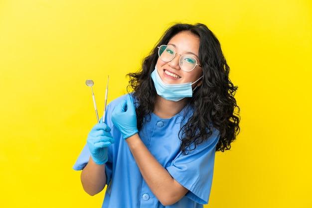 勝利を祝う孤立した背景の上にツールを保持している若いアジアの歯科医