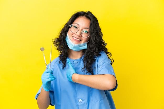 親指を立てるジェスチャーを与える孤立した背景の上にツールを保持している若いアジアの歯科医
