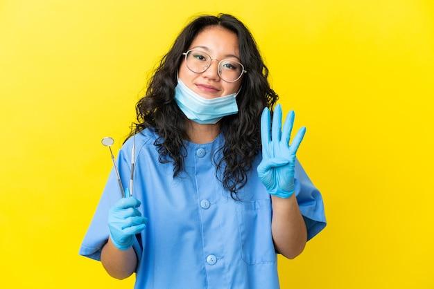 幸せな孤立した背景の上にツールを保持し、指で4を数える若いアジアの歯科医