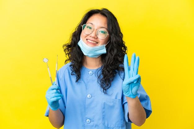 幸せな孤立した背景の上にツールを保持し、指で3を数える若いアジアの歯科医