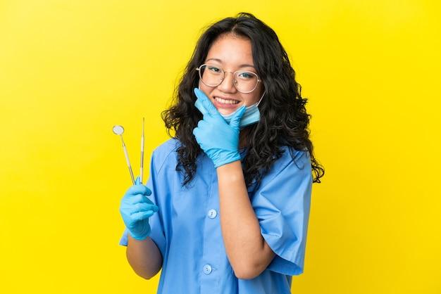 幸せと笑顔の孤立した背景の上にツールを保持している若いアジアの歯科医