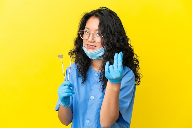 お金のジェスチャーを作る孤立した背景の上にツールを保持している若いアジアの歯科医