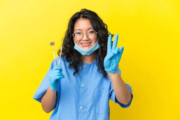 笑顔と勝利のサインを示す孤立した背景の上にツールを保持している若いアジアの歯科医