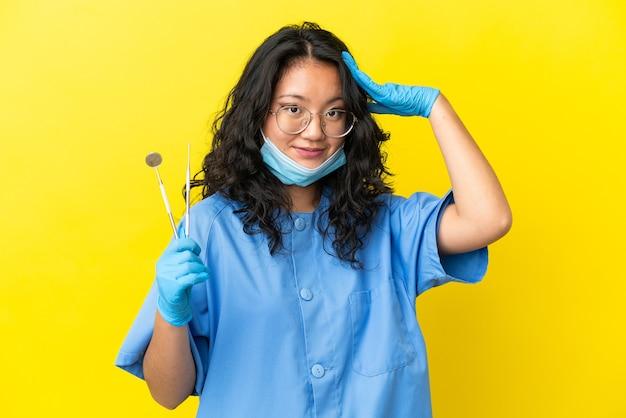 驚きの表現と孤立した背景の上にツールを保持している若いアジアの歯科医